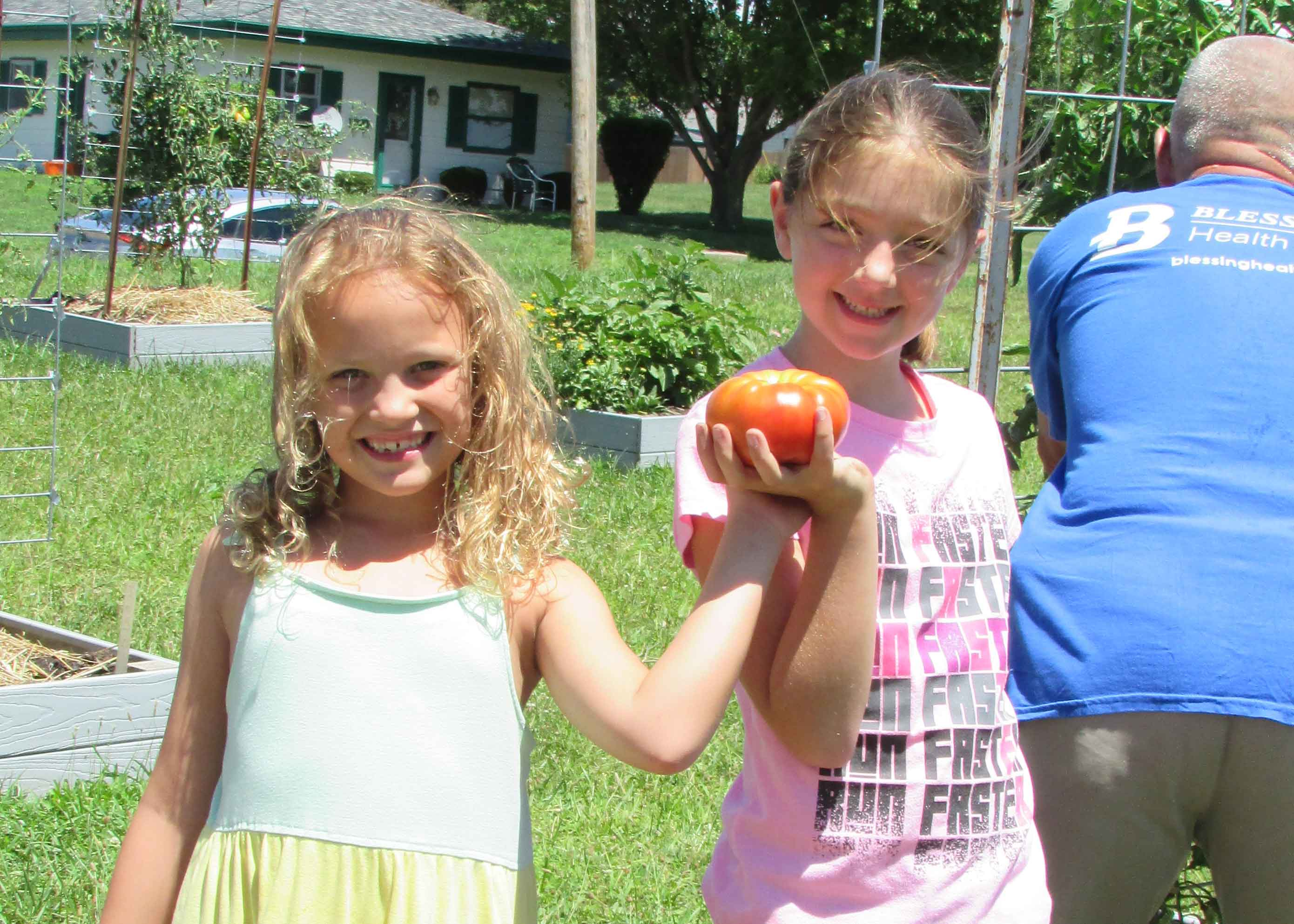 children in community garden with tomato